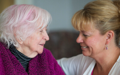 Caregiver helping Memory Care resident